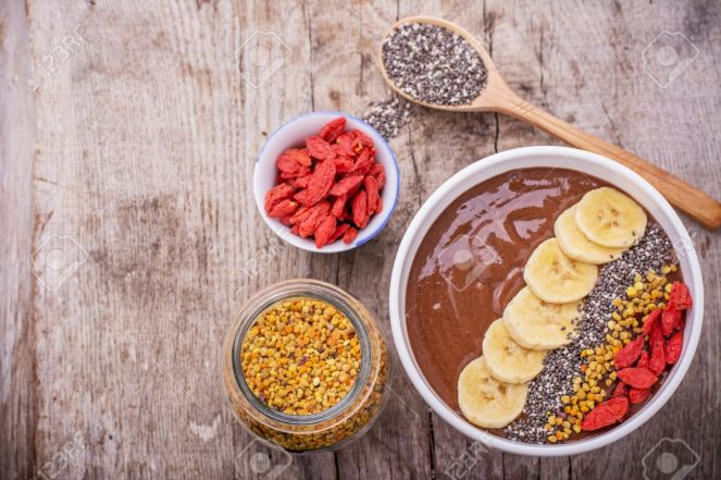 bowl of breakfast with chocolate banana smoothies garnished  bee pollen, chia seeds,